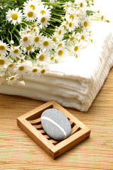 Zen stones with daisy on white towel