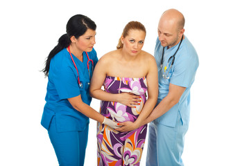 Doctors helping pregnant in pain