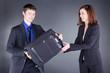 Geschäftsmann übergiebt Koffer Geschäftsfrau