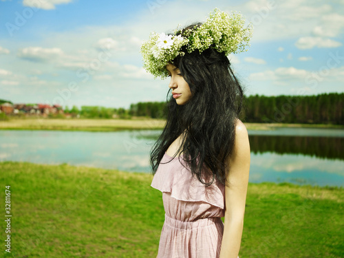 Beautiful girl wearing a wreath of wildflowers
