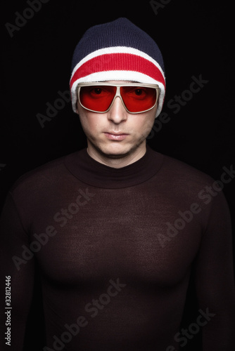 Young man in red and blue hat with sunglasses on black