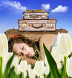 Traveling young woman resting in a tulip field