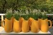 Mesa con jarrones amarillos y flores