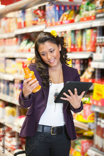 Woman looking at a product while holding digital tablet in shopp