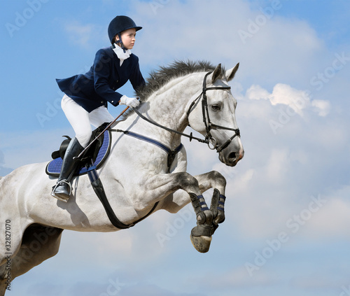 Equestrian jumper - young girl jumping with dapple-grey horse