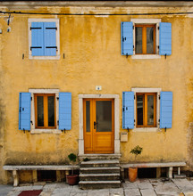 Front of an old house with blue shutters and yellow wall