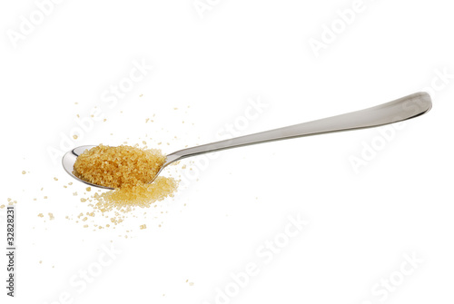 Golden demerara  sugar spilled from teaspoon isolated on white