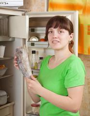 woman putting  frozen fish into fridge