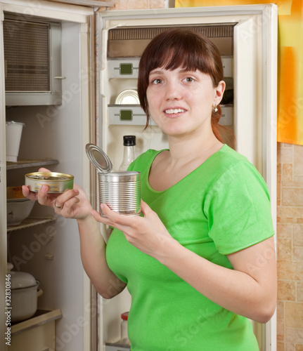 woman putting with metal can near fridge