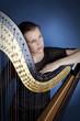 junge Frau mit Harfe in Gedanken versunken