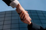Handshake unrecognizable business man and woman modern building poster