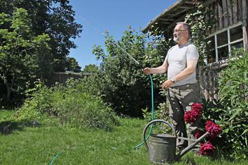Mann wässert Rasen