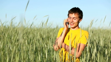 Man speaking cellphone in wheat field