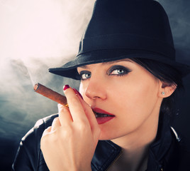 Attractive brunette in a felt hat smoking a cuban cigar