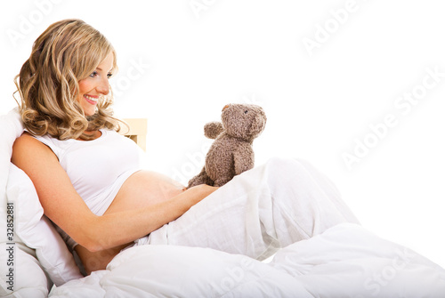 Pregnant woman in bed isolated on white