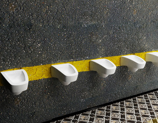 urinals in a row, public toilet