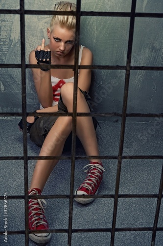 Punk girl showing middle finger behind bars