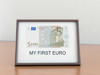 "Five euro in the a frame with the inscription ""My first euro"""