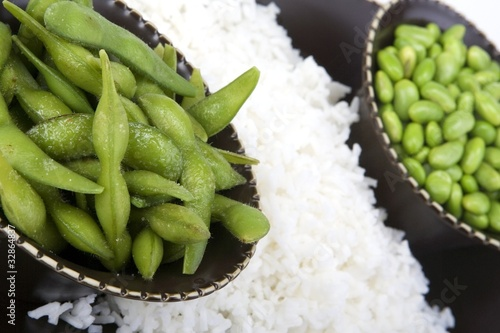 Edamame soy beans with white rice in a brown ceramic dish