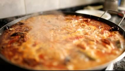 Paella cociendose, comida española arroz