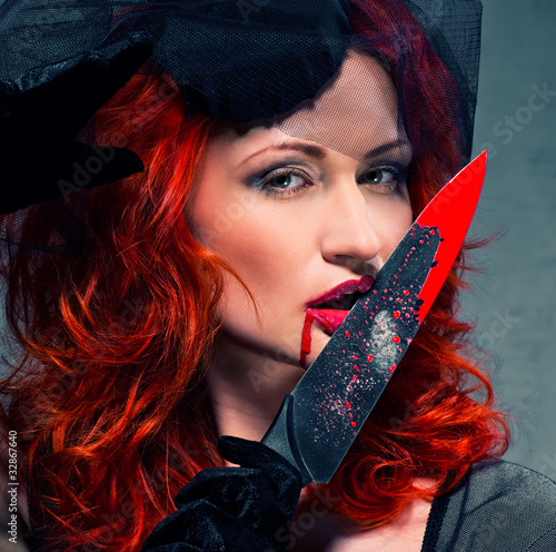 Gorgeous redhead woman with bloody knife in her hand close-up