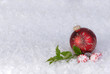 christmas ornament on snow with candy  and holly
