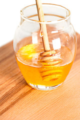 Fresh honey in glass jar on wooden table