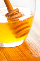Macro of fresh honey in glass jar on wooden table