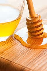 Drops of fresh honey, dipper and glass jar on wooden table