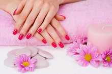 Spa manicure z różowymi kwiatami, kamieniami i świeca