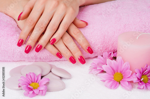 Spa manicure with pink flowers, stones and candle