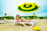 Beautiful woman laying on the beach under umbrella