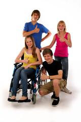 vier teenager daumen hoch rollstuhl