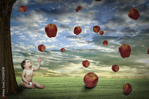 child sitting under an apple tree on green field