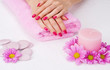 Spa manicure treatment with pink flowers, stones and candle