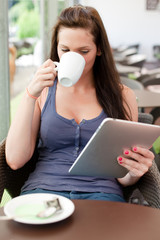 Coffee break and reading an article on her tablet