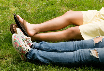 legs of teen couple lying in the grass
