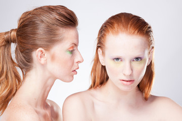 Two beautiful red-haired woman confront