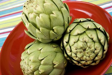 Raw artichokes on a red ceramic plate with colorful background