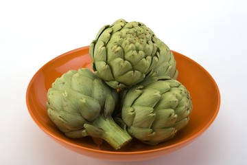 Raw artichokes in an orange ceramic bowl