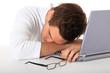 Junger Mann ist am Schreibtisch eingeschlafen