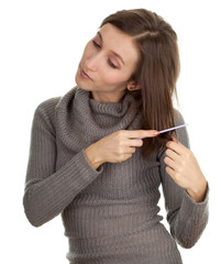 combing smiling young woman in grey sweater