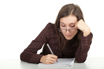 young woman in eyeglasses writing on blank card