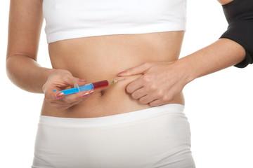 slim girl giving herself insulin shot; isolated