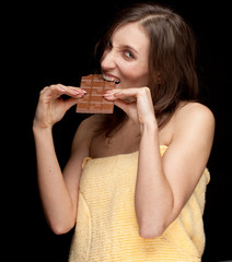young woman in towel eating chocolate, black background .