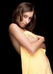 young long hair woman in yellow towel, black background