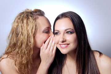 Young woman sharing secret to her friend
