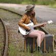 Mädchen mit Gitarre wartet auf Zug