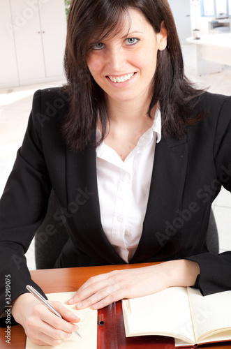 Smiling businesswoman writing on her agenda