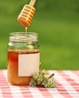 Jar of honey against nature background